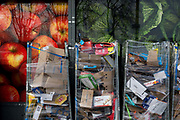 Detail of supermarket packaging and assorted materials being stored in bins outside a local Co-Op in Bellingham, on 5th February 2020, in London, England. The industrial bins are parked in front of the supermarket posters that shows fresh fruit of red apples and cabbages, and have been wrapped in plastic cling-film to contain the many boxes stacked up and awaiting collection by a recycling provider.