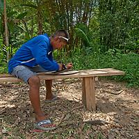 A young man planes a canoe paddle in San Juan de Yanayacu village in Peru's Amazon Jungle.