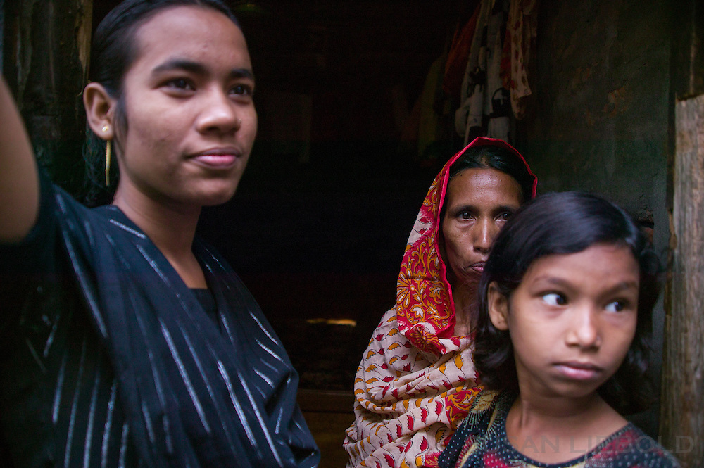 Jalal's wife with two of his daughters at the entrance to their home.