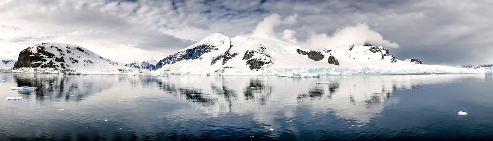 A high resolution panorama of mountains reflected on calm waters near the entrance of Neko Harbour on the western coast of the Antarctic Peninsula.