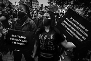 People gather during a demonstration to show solidarity with the Black Lives Matter movement in Brussels, Belgium, Women wear a protective face mask and hold a placard, June 07, 2020.