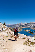 A backpacker ascends to Selden Pass, with Marie Lake in the background; along the John Muir Trail; John Muir Wilderness, Sierra National Forest, Sierra Nevada Mountains, California, USA.