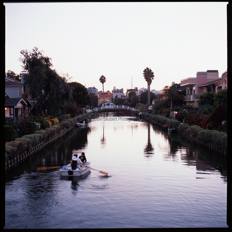 """People enjoy evening rowing as dusk falls on the Venice Canals in Los Angeles, California.  """"Venice of America"""" was founded by tobacco millionaire Abbot Kinney in 1905 and was modeled after those in Italy."""