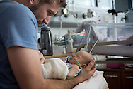 Philip Jones from Canterbury, Kent, cradles his three-day-old son Finn, at Evelina Children's London Hospital Hospital neonatal intensive care unit in central London. Finn was born with a pre-diagnosed condition which required a life-saving, five-hour heart 'switch' operation to be carried out within the first two weeks of his life. The operation, which took place when Finn was 10 days old was successful, however, due to other near fatal complications the his recovery during the subsequent six weeks was slow and difficult.