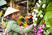 27 MARCH 2012 - HO CHI MINH CITY, VIETNAM: A flower vendor finishes a display in Ben Thanh Market, the main market in Ho Chi Minh City, Vietnam. The market has become the main tourist market. Ho Chi Minh City, which used to be known as Saigon, is the largest city in Vietnam and the commercial hub of southern Vietnam.      PHOTO BY JACK KURTZ