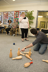 Care worker pointing out a rule of the game to a woman taking part in an indoor bowling group of Day service users with learning disabilities,