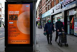 © Licensed to London News Pictures. 26/10/2020. London, UK. Shoppers wearing face coverings walk past a COVID-19 high alert level sign in north London. It has been reported that the government is planning for an extra tougher fourth tier of Covid-19 restrictions in England if coronavirus cases increase in the coming weeks. The measures could see restaurants, pubs and non-essential businesses such as clothes shops forced to close in areas where tier 3 rules have not brought the virus under control. Currently all 32 boroughs plus the City of London are in tier two, where there is a high risk of coronavirus. Photo credit: Dinendra Haria/LNP