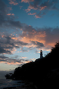 The setting sun lights up the clouds behind the Diamond Head Lighthouse on Oahu.
