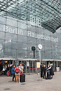 Berlin, Germany - September 3, 2015: People stand with luggage outside the Berlin Hauptbahnhof (main train station) in Berlin, Germany.