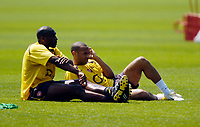 Photo: Richard Lane.<br />Arsenal Training Session. The Barclays Premiership. 11/05/2006.<br />Sol Campbell (L) and Thierry Henry take a rest during training.