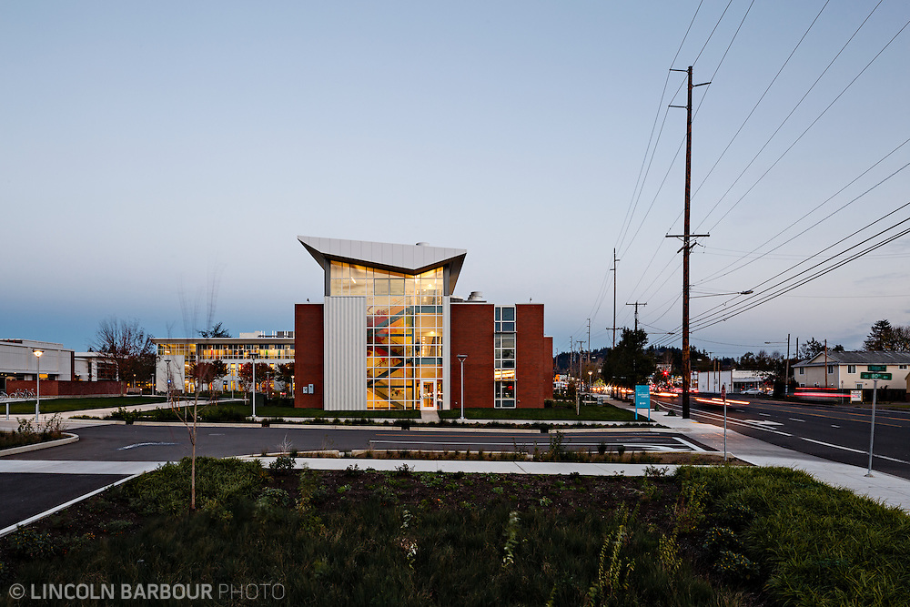 A modern looking community college building at dusk with car lights streaking by and lights glowing from the interior.