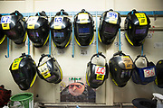 Numbered welding helmets hanging on the Wall inside the metal work training centre of the industries department at  HMP Featherstone, Wolverhampton, Staffordshire United Kingdom. HMP Featherstone is a Category C adult male training prison with a population of around 700 and operated by HM Prison Services. (Picture credit: © Andy Aitchison)