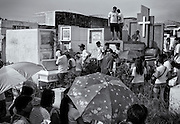 Philippines has a high mortality rate and in Manila area, 5 people die for each 1000, making funerals very common.<br /> A wife and brother of the deceased mourn next to grave, while family and friends take position between graves and give a last tribute to the person who died.