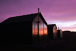 © Licensed to London News Pictures. <br /> 07/01/2015. <br /> <br /> South Gare, Teesside<br /> <br /> The pink light of morning lights up the huts at the South Gare Fisherman's Association at Redcar in Cleveland.<br /> <br /> Photo credit : Ian Forsyth/LNP