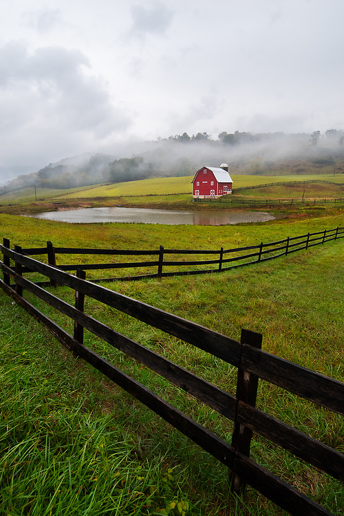 A photogenic red barn sits against a backdrop of fog on a rainy evening near Marlinton and Edray, West Virginia.