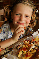 ten year old girl eating french fries - photograph by Owen Franken