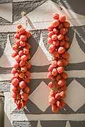 Close up of tomatoes drying on wall of house decorated in traditional patterns, Pyrgi, Chios, Greece