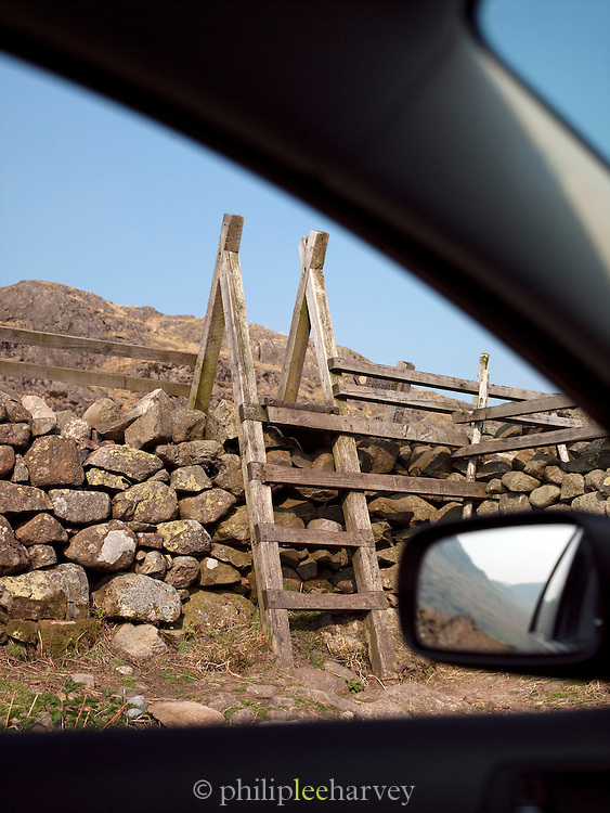 An old wooden step ladder over an old stone wall in the Lake District, UK