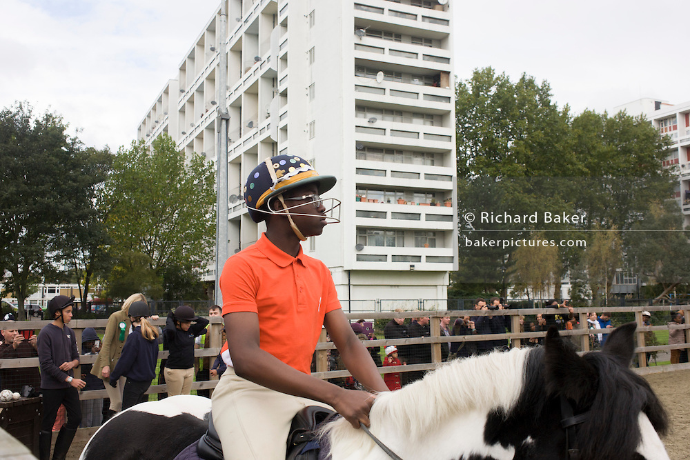 A young horse rider parades around the equestrian ring while Queen Elizabeth makes a brief visit to the Ebony Horse Club at Loughborough Junction, Brixton, London. Accompanied by the Duchess of Cornwall, Her Majesty watched an equestrian demonstration in one of the most disadvantaged inner city neighbourhoods in the country where there is a historic legacy of under-achievement in schools, high rates of teenage pregnancy and negative stereotypes of young people, gang violence and drug related crime.