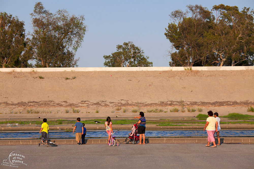 Residents keeping cool on a hot Summer evening by walking along the Los Angeles River, Bell, Los Angeles County, California, USA