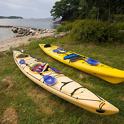 Sea kayaks on the shoreline og Eggemoggin Reach at the Oakland House Seaside Resort in Brooksville, Maine.  Blue Hill Peninsula.  East Penobscot Bay.