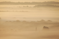 © Licensed to London News Pictures. 28/09/2015. Near Dorking, UK. Brockham church spire is seen above fog covering the landscape as the sun rises.  Photo credit: Peter Macdiarmid/LNP