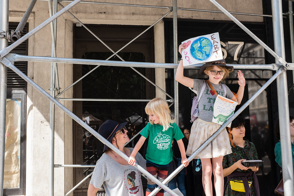 "20 September 2019 - New York, NY.  Thousands of students as well as adults gathered in New York for the Global Climate Strike, meeting in Foley Square near the Federal Government buildings and New York's City Hall, and marching downtown to Battery Park, where Swedish climate activist and spokesperson Greta Thunberg addressed the crowd. A young family watches the march from beneath scaffolding on Broadway. One girl holds a sign reading ""Save Earth"" and wears another reading ""dinosaurs = extinct."""