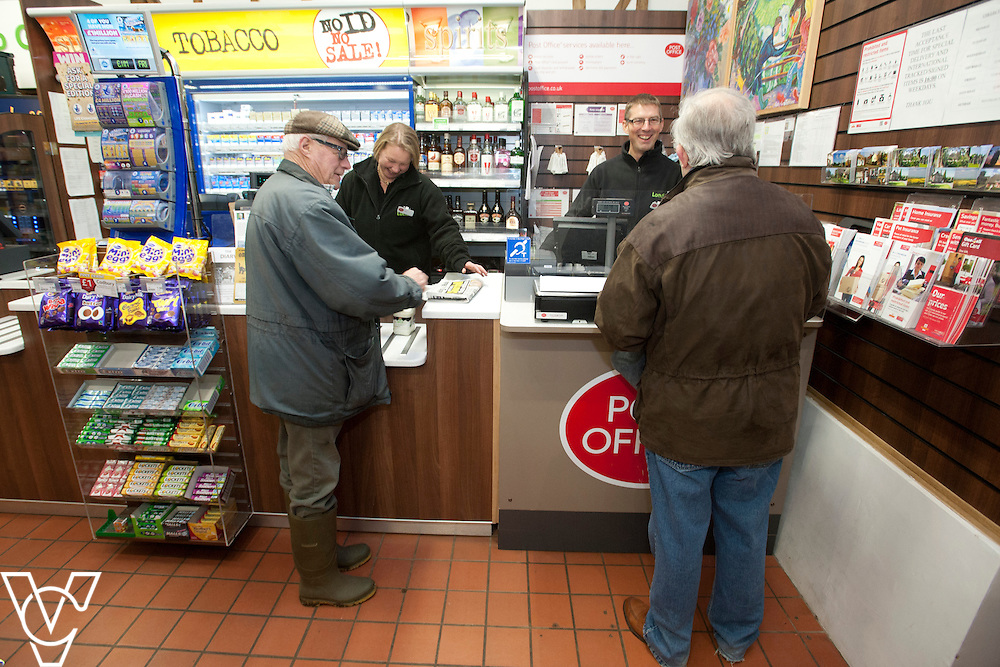 Pictured is, from left, customer Brian Crouch being served by Lisa Storey and postmaster Dave Bray serving customer Stuart White<br /> <br /> Barley Post Office, Church End, Royston, Hertfordshire.<br /> Date: January 23, 2015