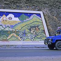 CHINA, TIBET. Chinese truck passes Tibetan Buddhist mural on road cut near Tsedang & Yarlung Tsangpo River.