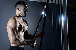 Muscular man doing triceps exercise at gym