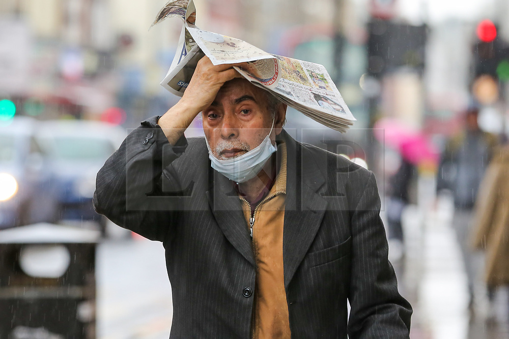 © Licensed to London News Pictures. 09/10/2020. London, UK. A man shelters from rain underneath Metro newspaper in north London. According to the Met Office more rain is forecast for the weekend. Photo credit: Dinendra Haria/LNP
