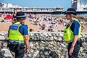 Police community support officers patrol the beach checking to see if large groups come from the same houshold- if not they ask them to observe the 2m rule. It is sunny and people come to the beach and the seaside at Brighton, during Bank holiday Monday. It is busy but still plentyu of room for social distancing. The eased 'lockdown' continues for the Coronavirus (Covid 19) outbreak.