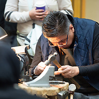 Jeweler Lyndon Tsosie, 50, lines a stamp into position during his demonstration at UNM-Gallup Gurley Hall on Wednesday.