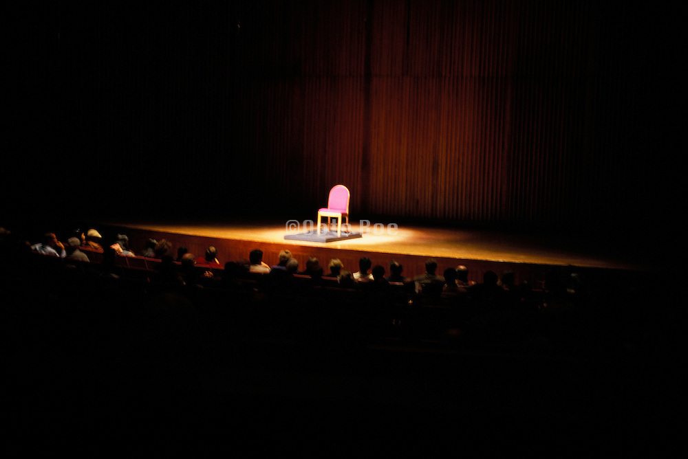 Stage with an empty chair on a podium waiting for the performer.