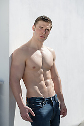 rugged shirtless muscular man against a white wall
