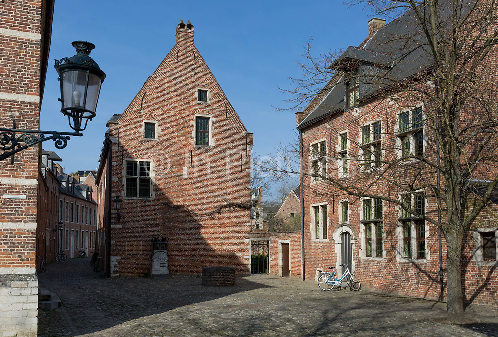 The protected UNESCO World heritage Site at the Grand Beguinage in the historic city of Leuven, on 24th March 2017, in Belgium. The Grand Béguinage of Leuven, or in Dutch Groot Begijnhof van Leuven is a well preserved and completely restored historical quarter containing a dozen streets south of the city. About 3 hectares 7.5 acres in size, with some 300 apartments in almost 100 houses, it is one of the largest remaining béguinages in the Low Countries. Founded in 1232, it was a community for women Beguines, widows or spinsters wishing for a religious but independent life. It is now an area for professors, students and staff of Leuven University.