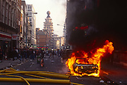 A Porsche car burns fiercely outside the theatre where Will Russels Blood Brothers is showing, during the Poll Tax riot in the UK capital, on 31st March 1990, in St. Martins Lane, London, England. Angry crowds, demonstrating against Margaret Thatchers local authority tax, stormed the Whitehall area and then Londons West End, setting fire to a construction site and cars, looting stores up Charing Cross Road and St Martins Lane. The anti-poll tax rally in central London erupted into the worst riots seen in the city for a century. Forty-five police officers were among the 113 people injured as well as 20 police horses. 340 people were arrested.