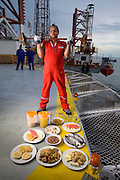 """Oswaldo Gutierrez, Chief of the PDVSA Oil Platform GP 19 in Lake Maracaibo, Venezuela with his typical day's worth of food. (From the book What I Eat: Around the World in 80 Diets.) The caloric value of his day's worth of food on a day in December was 6000 kcals. He is 52; 5'7"""" and 220 pounds. Gutierrez works on the platform for seven days then is off at home for seven days.   While on the platform he jogs on its helipad, practices karate, lifts weights, and jumps rope to keep fit. His food for the seven days comes from the platform cafeteria which, though plagued with cockroaches, turns out food choices that run from healthful to greasy-fried. Fresh squeezed orange juice is on the menu as well and Gutierrez drinks three liters of it a day himself. His diet changed about ten years ago when he decided that he'd rather be more fit than fat like many of his platform colleagues. PDVSA is the state oil company of Venezuela. MODEL RELEASED."""