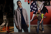 A workman talking on his smartphone walks past a H&M and Uniqlo menswear poster outside central London shop. The models on the poster are perfect ideals, models of perfection while the person on the street is a working man dressed in working clothes from a neaby building site. UNIQLO is a clothing apparel company, which was originally founded in Yamaguchi, Japan in 1949 as a textiles manufacturer. Now it is a global brand with over 1000 stores around the world. Redefining clothing, with a focus on quality and textiles which has been unwavered since the company's origins in 1949.