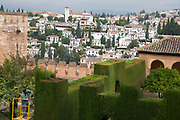 The Alhambra Palace and fortress complex located in Granada, Andalucia, Spain. Worker cutting the sculpted topiary hedges.
