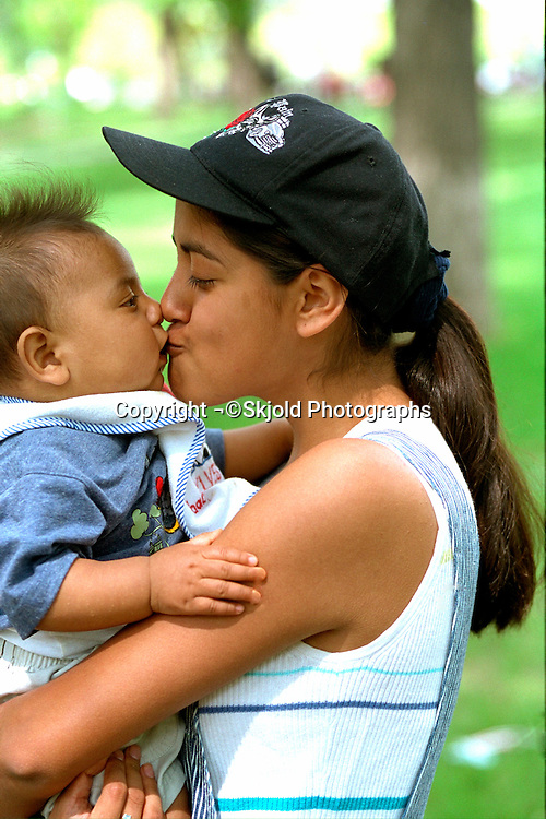 Mother and son ages 23 and 3 months kissing at walk for AIDS fundraiser.  Minneapolis Minnesota USA