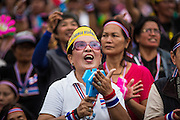 """15 NOVEMBER 2013 - BANGKOK, THAILAND: An anti-government protester applauds during a protest rally in Bangkok. Tens of thousands of Thais packed the area around Democracy Monument in the old part of Bangkok Friday night to protest against efforts by the ruling Pheu Thai party to pass an amnesty bill that could lead to the return of former Prime Minister Thaksin Shinawatra. Protest leader and former Deputy Prime Minister Suthep Thaugsuban announced an all-out drive to eradicate the """"Thaksin regime."""" The protest Friday was the biggest since the amnesty bill issue percolated back into the public consciousness. The anti-government protesters have vowed to continue their protests even though the Thai Senate voted down the bill, thus killing it for at least six months.      PHOTO BY JACK KURTZ"""