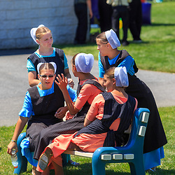 Intercourse, PA - June 18, 2016: Amish teenage girls sit on a bench in the Community Park at the Intercourse Heritage Days event.