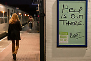 A female rail traveller walks along the platform at Loughborough Junction railway station where a Samaritan's poster urges those with mental health issues, or even thoughts of suicide, to seek help from the registered charity aimed at providing emotional support to anyone in emotional distress, struggling to cope, or at risk of suicide throughout the United Kingdom and Ireland, often through their telephone helpline, on 27th February 2021, in London, England.