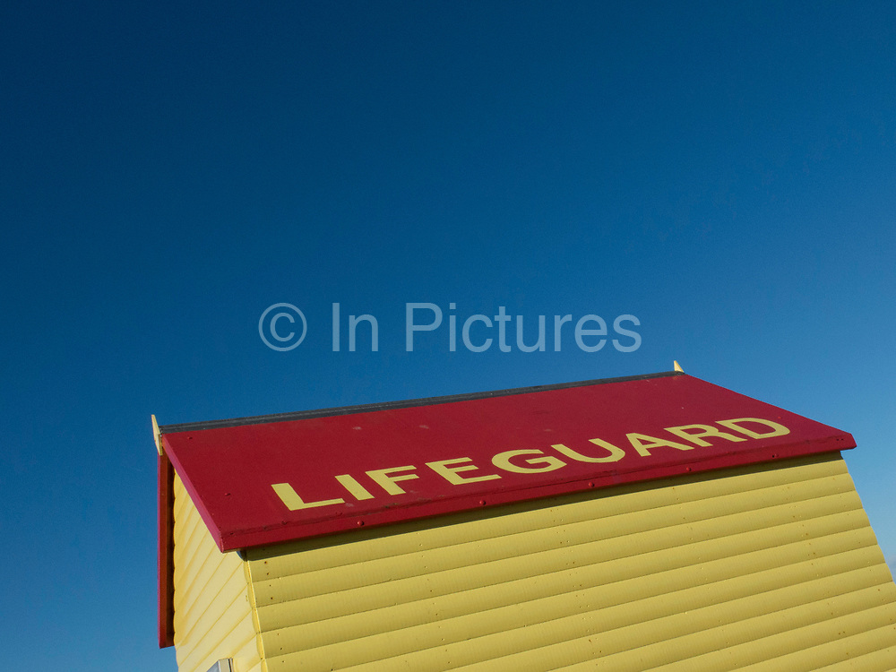 Lifeguards beach hut and blue sky in Whitstable, United Kingdom. Whitstable is a seaside town on the north coast of Kent in south-east England. Whitstable is famous for oysters, which have been collected in the area since Roman times and are celebrated at the annual Whitstable Oyster Festival.
