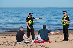 Portobello, Scotland, UK. 20 May 2020. Hot sunny weather brought out large crowds to Portobello beach today. Lockdown discipline seems to be a thing of the past with families and friends hitting the sand. A heavier than normal police presence had little visible effect since the public returned to the sand after the police walked away.  Police confront two angry drunk men who were resisting efforts to move them along. Iain Masterton/Alamy Live News