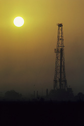 Silhouette of an oil and gas drilling rig at sunset in Texas hayfield.
