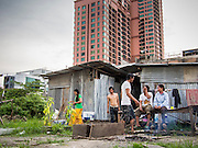 05 SEPTEMBER 2013 - BANGKOK, THAILAND:  Cambodian workers relax around their cooking fire after their construction shift at the construction site of a new high rise apartment / condominium building on Soi 22 Sukhumvit Rd in Bangkok. The workers live in the corrugated metal dorms on the site. Most of the workers at the site are Cambodian immigrants.             PHOTO BY JACK KURTZ
