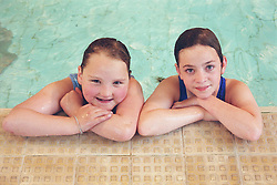 Young girl with complex congenital heart disease resting on side of public swimming pool next to young girl with learning disabilities,