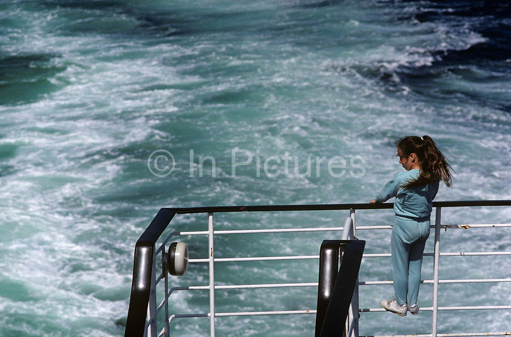 As the wake from a ship foams behind the vessel, a young girl stands on some railings of a cross-Channel ferry that is sailing between Dover in England and Calais in France. Holidaymakers take their vehicles to continental Europe and foot passengers go on foot. The child stands and grips the rails as the sea is left disturbed by the boat's propellers. It's not a safe place for a young person to stand, so near the edge of the ship and the water below. She looks at the sea and imagines her holiday adventure that is beginning. People do fall overboard on these voyages and children need to be supervised so close to danger.